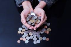 La femme d'affaires a des mains complètement des pièces de monnaie Photos stock