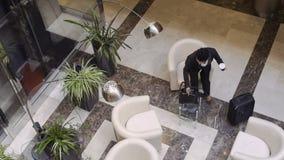 La femme d'affaires est juste arrivée dans un hôtel et s'assied vers le bas dans le fauteuil dans le hall de lobby clips vidéos