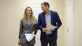 La femme d'affaires et un homme marchent le long du couloir et de parler images stock