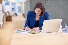 La femme d'affaires faisant des notes à son bureau avec l'ordinateur portable s'ouvrent photographie stock libre de droits