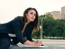 La femme d'affaires fait des notes en ses papiers d'affaires photos stock