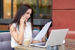 La femme d'affaires focalisée lit des papiers d'affaires attentivement, reçoit la consultation par l'intermédiaire du téléphone p photos libres de droits