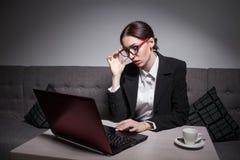 La femme d'affaires habillée dans le costume et avec l'ordinateur portable a la pause-café ; Photographie stock libre de droits