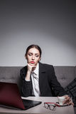 La femme d'affaires habillée dans le costume et avec l'ordinateur portable a la pause-café ; Images libres de droits