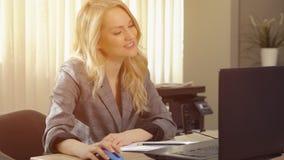 La femme d'affaires heureuse dans le costume travaille à l'ordinateur dans le bureau photo libre de droits