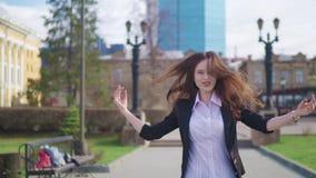 La femme d'affaires heureuse est marchante et dansante dans la rue regardant l'appareil-photo Happynes célébrez la réussite banque de vidéos