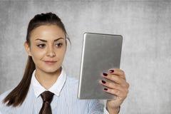 La femme d'affaires lit calmement l'information sur l'Internet dessus il Photo libre de droits