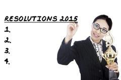 La femme d'affaires lui écrit des résolutions en 2015 Photographie stock libre de droits