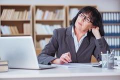 La femme d'affaires mûre travaillant dans le bureau Photographie stock