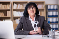 La femme d'affaires mûre travaillant dans le bureau Image libre de droits