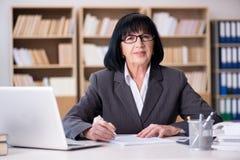 La femme d'affaires mûre travaillant dans le bureau Photo libre de droits