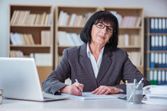 La femme d'affaires mûre travaillant dans le bureau Photo stock
