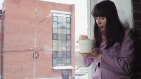 La femme d'affaires mange les nouilles instantanées se reposant sur le rebord de fenêtre contre l'immeuble de brique banque de vidéos
