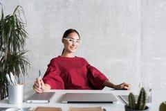 La femme d'affaires mignonne positive se repose dans le bureau Image libre de droits