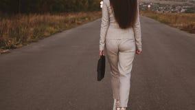 La femme d'affaires mince avec la serviette noire dans sa main entre dans le pantalon et des chaussures à talons hauts blanches s banque de vidéos