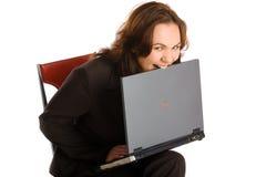 La femme d'affaires mordent hors fonction l'ordinateur portatif photo libre de droits