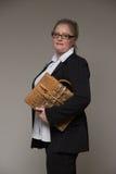 La femme d'affaires n'est pas jeune dans un costume avec une serviette en cuir Image stock