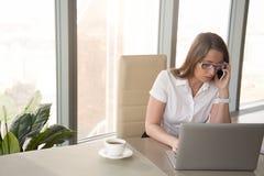 La femme d'affaires occupée sérieuse s'est concentrée sur la conversation mobile, talki Photographie stock