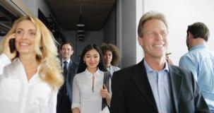 La femme d'affaires parlant sur l'appel téléphonique marchant avec des gens d'affaires de course de mélange team par l'immeuble d clips vidéos