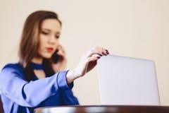 la femme d'affaires parle le téléphone dans le bureau et en travaillant sur l'ordinateur portable images stock