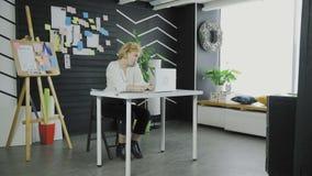 La femme d'affaires parle sur son smartphone tout en dactylographiant sur le carnet banque de vidéos