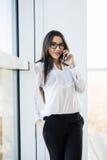La femme d'affaires parlent du téléphone près de grandes fenêtres de bureau Photo stock