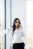 La femme d'affaires parlent du téléphone près de la grande fenêtre de bureau Image libre de droits