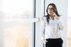 La femme d'affaires parlent du téléphone près de la grande fenêtre de bureau Images stock