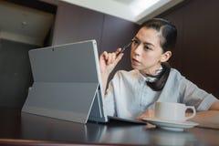 La femme d'affaires pensant le nouveau plan de travail d'idée, prise parquent en main se reposer utilisant l'ordinateur portable  Image stock