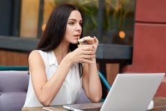 La femme d'affaires réfléchie a la pause-café dans le cafétéria extérieur, utilise l'ordinateur portable pour le travail éloigné, image libre de droits