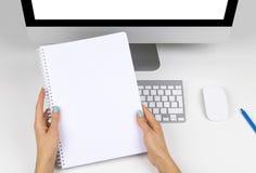 La femme d'affaires remet tenir le carnet avec l'espace pour le texte Lieu de travail d'affaires avec l'ordinateur avec l'écran v Photos stock