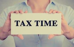 La femme d'affaires remet tenir le signe de carte avec le message de temps d'impôts Image stock