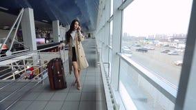 La femme d'affaires reste dans l'aéroport et parle au téléphone portable clips vidéos