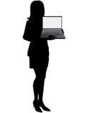 La femme d'affaires retient l'ordinateur portable pour afficher Photographie stock