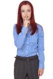 La femme d'affaires rousse retient le doigt sur ses languettes Photo libre de droits