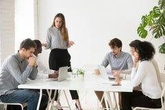 La femme d'affaires sérieuse grondant des employés pour des pauvres travaillent des résultats Image stock