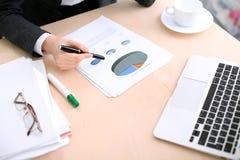 La femme d'affaires s'asseyant à la table et examine les bilans financiers Photo libre de droits