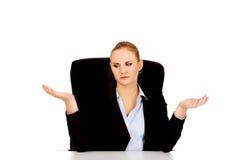 La femme d'affaires s'asseyant derrière le bureau et faisant ne savent pas chantent Photo libre de droits