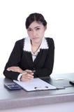 La femme d'affaires s'asseyant sur son bureau tenant un stylo fonctionnant avec font Photos libres de droits