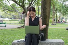 La femme d'affaires s'asseyent dans le jardin et sa tête étreinte par main, le sentiment de soumis à une contrainte et tristesse  photos stock