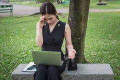 La femme d'affaires s'asseyent dans le jardin et sa tête étreinte par main, le sentiment de soumis à une contrainte et tristesse photo stock