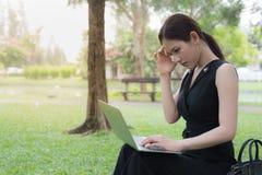 La femme d'affaires s'asseyent dans le jardin et sa tête étreinte par main, le sentiment de soumis à une contrainte, tristesse ou photographie stock libre de droits