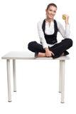 La femme d'affaires s'asseyent sur la table avec la pomme image stock