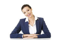 La femme d'affaires s'assied au bureau Photographie stock libre de droits