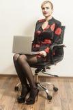La femme d'affaires s'assied sur la chaise avec son ordinateur portable image libre de droits