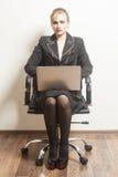 La femme d'affaires s'assied sur la chaise avec son ordinateur portable images libres de droits