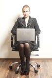 La femme d'affaires s'assied sur la chaise avec son ordinateur portable sur le backgro de papier peint photographie stock libre de droits