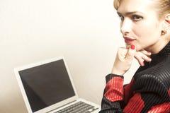 La femme d'affaires s'assied sur la chaise avec son ordinateur portable sur le backgro de papier peint images libres de droits