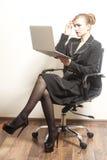 La femme d'affaires s'assied sur la chaise et le travail image stock