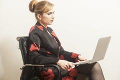 La femme d'affaires s'assied sur la chaise et le travail photos stock